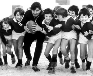 Rugby commentator, and former PE teacher, Bill McLaren leads a group of young rugby players in a charge at the photographer during a visit to a school in his home town Hawick